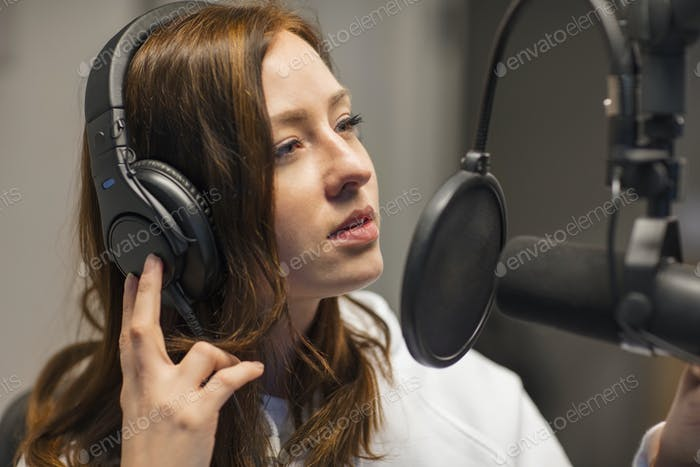 Jockey Listening Through Headphones In Radio Studio