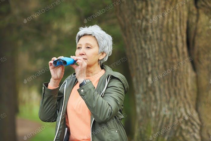 Mature Woman Looking in Binoculars during Hike