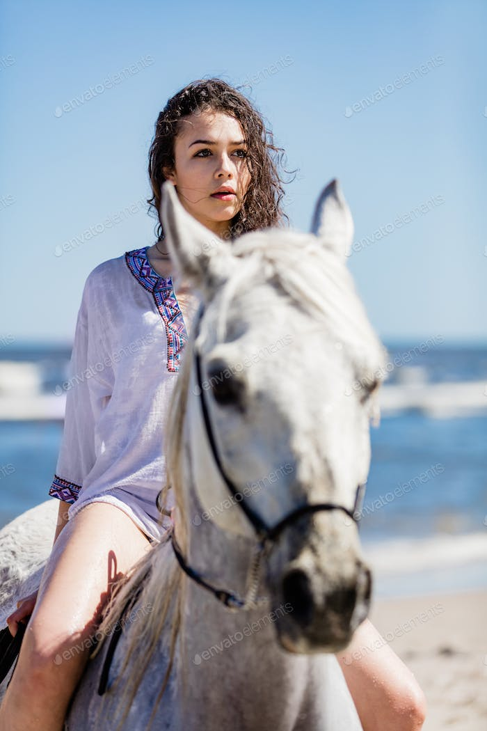 Young girl sitting on a white horse on the seashore