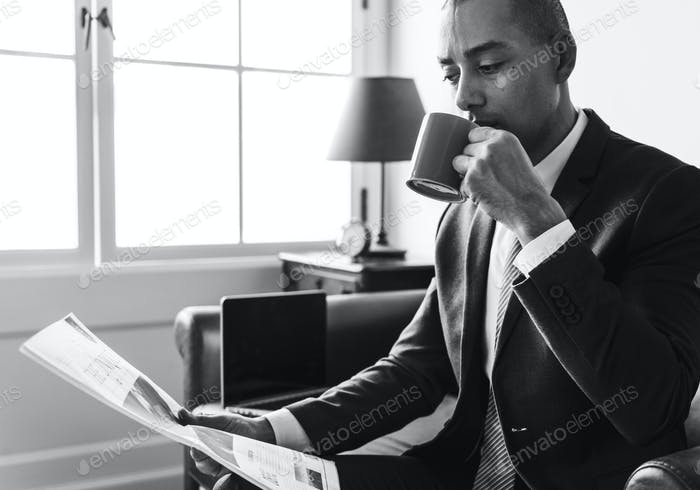 Businessman reading newspaper and having coffee