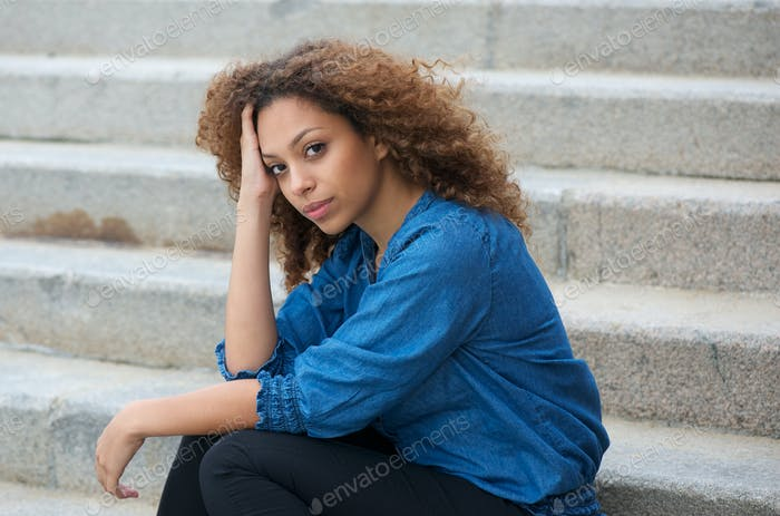Beautiful young woman sitting on stairs outdoors