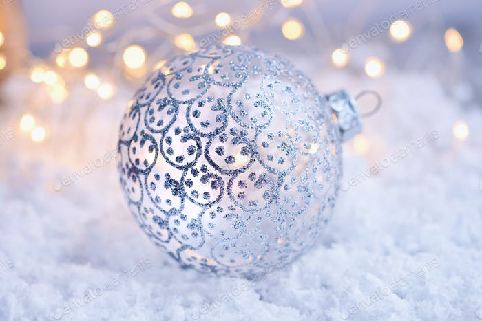 Christmas decorative ball on snow and Christmas lights. Festive