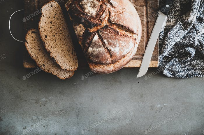 Freshly baked sourdough bread loaf and slices on wooden board