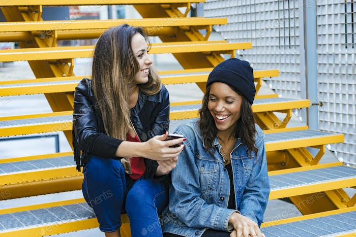two mixed race female friends sitting and taking a selfie