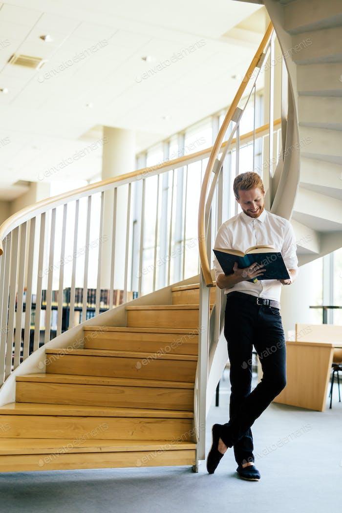 Hübscher intelligenter Kerl liest ein Buch in einer Bibliothek