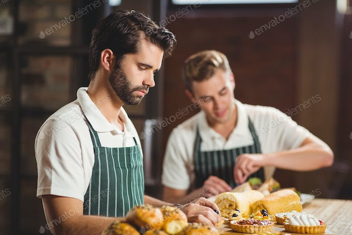 Concentrated waiters tidying up the pastries at the coffee shop