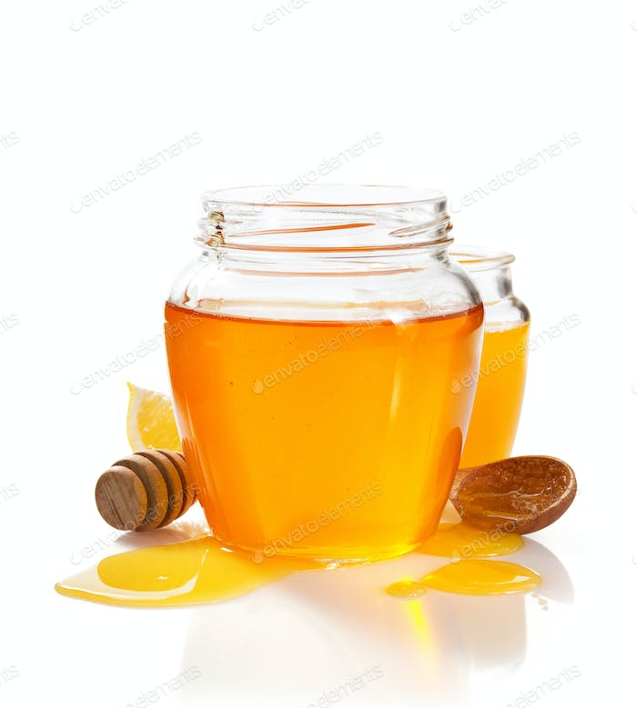 glass jar full of honey and dipper
