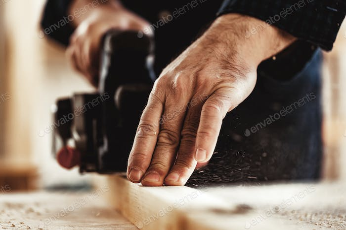 Carpenter's hands working with electric planer in a workshop