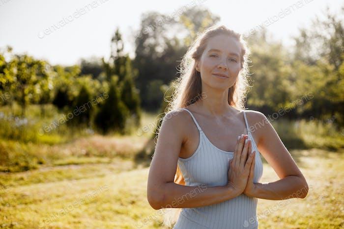 Junge Frau in Yoga-Kleidung praktiziert Yoga an der frischen Luft im Wald am sonnigen Tag