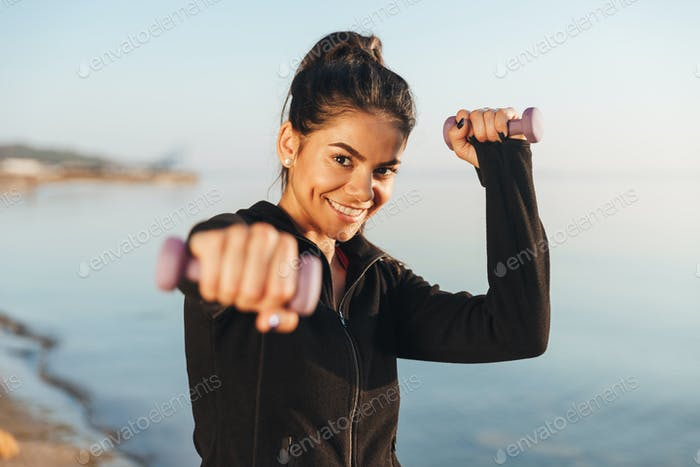 Cheerful young sportsgirl doing exercises with small dumbbells