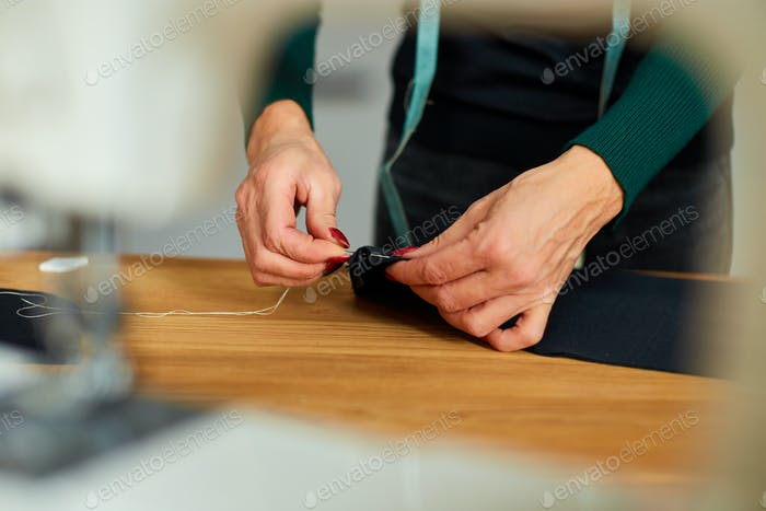 Step by step, 50-yers old woman sewing fabric with hand
