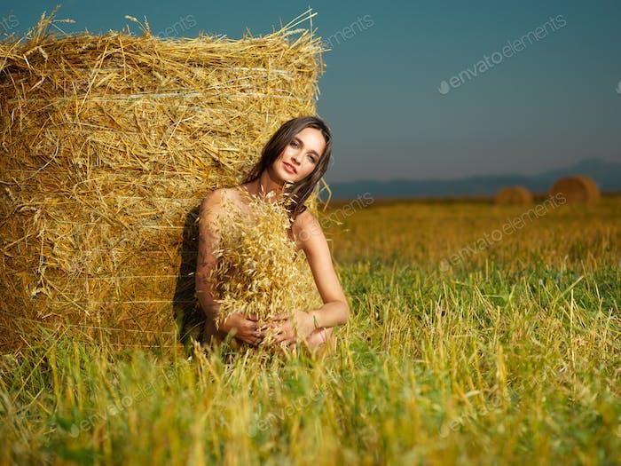 beautiful nude woman sitting near hay stack
