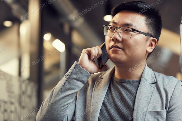 Asiatischer Geschäftsmann mit dem Smartphone