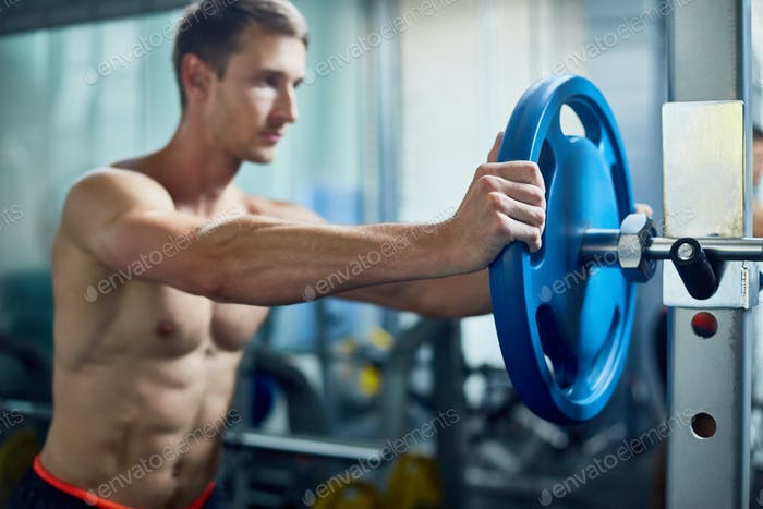 Strong Man Assembling Barbell in Gym