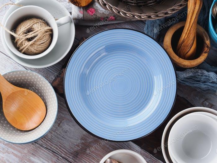 Ceramic and enamel crockery on wooden background