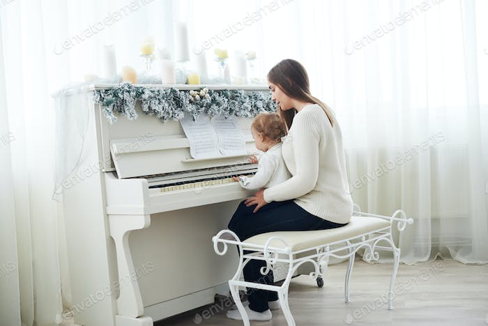 Look from behind at mother and daughter playing white piano