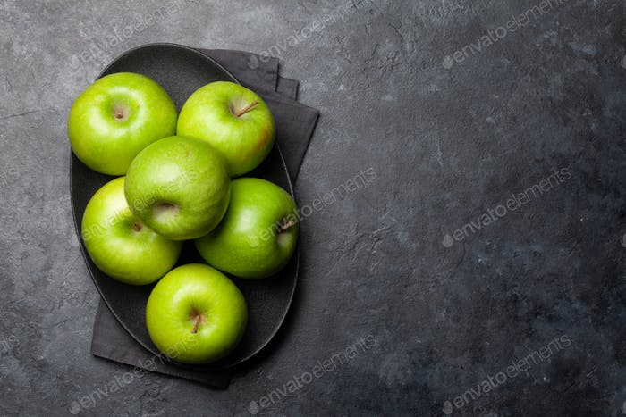 Ripe green apple fruits on dark stone table