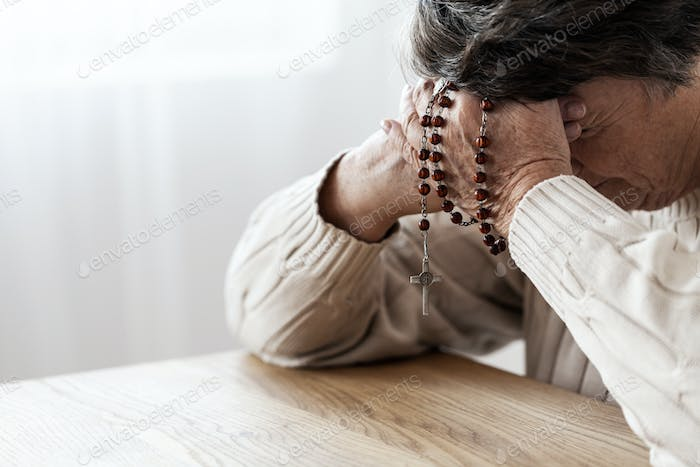 Elderly person in melancholy praying with rosary in church