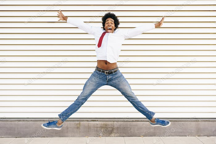 Black Businessman jumping outdoors. Man with afro hair