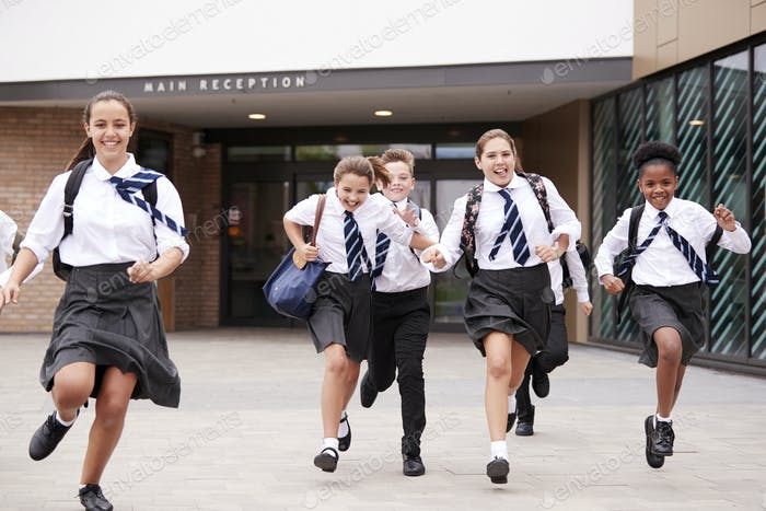 Group Of High School Students Wearing Uniform Running Out Of School Buildings