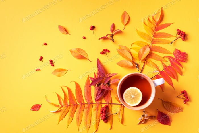 Autumn flat lay composition. Cup of tea, autumn bright leaves on yellow background. Top view. Flat
