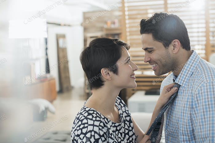 A woman adjusting a man's tie, smiling at him.