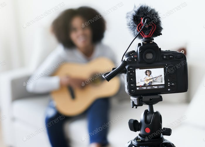 Female vlogger recording music related broadcast at home