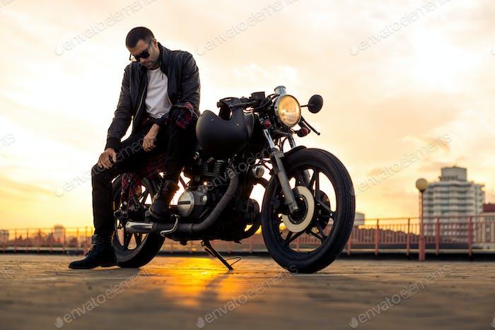 Brutal Mann sitzen auf Cafe Racer benutzerdefinierte Motorrad.
