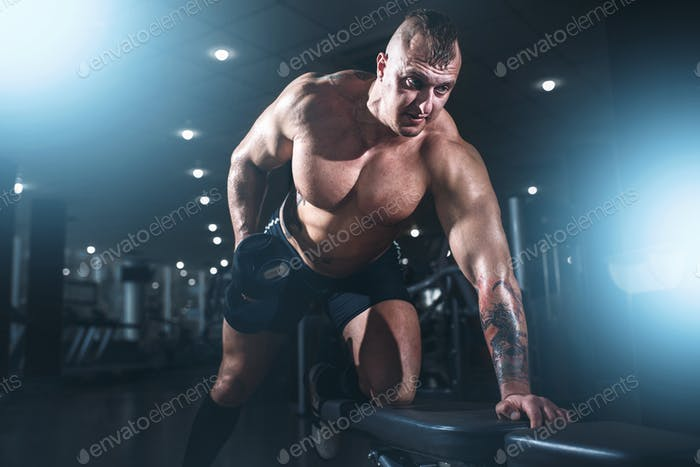 Athlete with muscular body lifting dumbbells