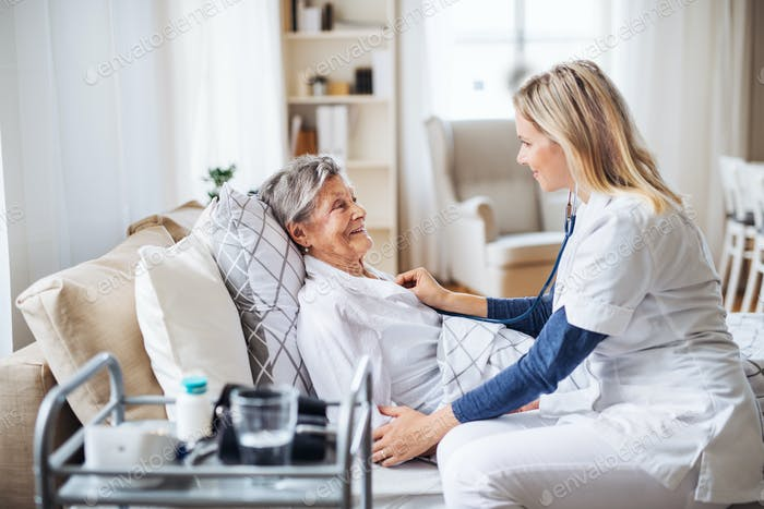 A health visitor examining a sick senior woman lying in bed at home with stethoscope.