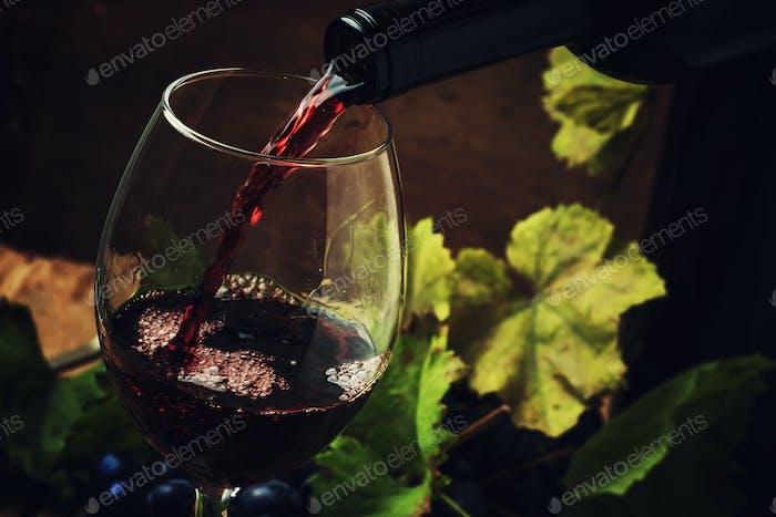 Rotwein in Glas gießen