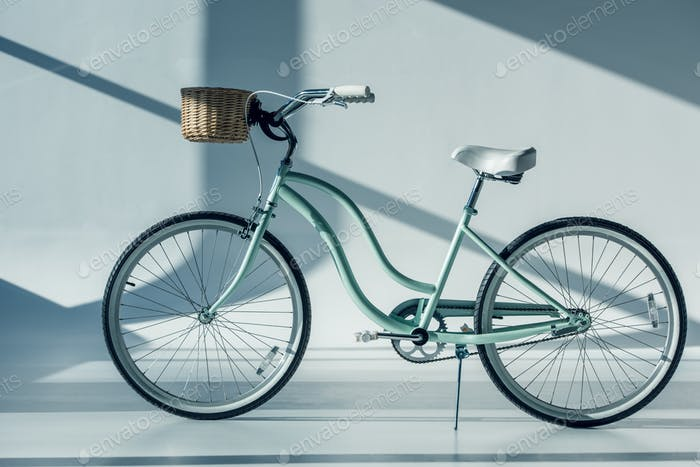 hipster bicycle with basket and shadows on white floor