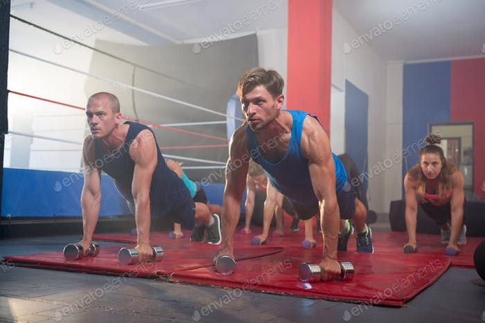 Young athletes practicing push ups on dumbbells by boxing ring