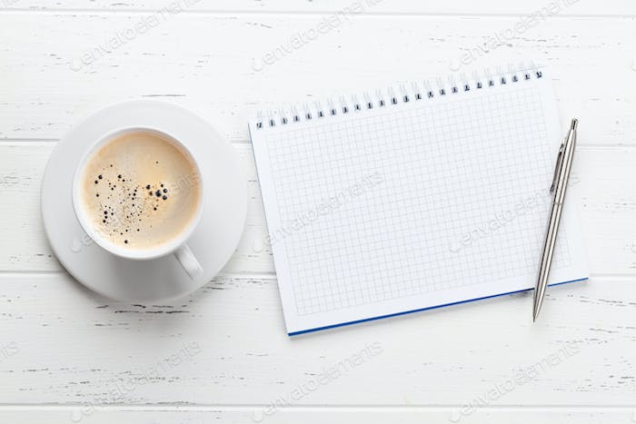 Office workplace table with notepad and coffee