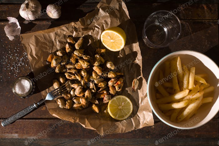 Mussels with lemons and French fries on the metal background top view