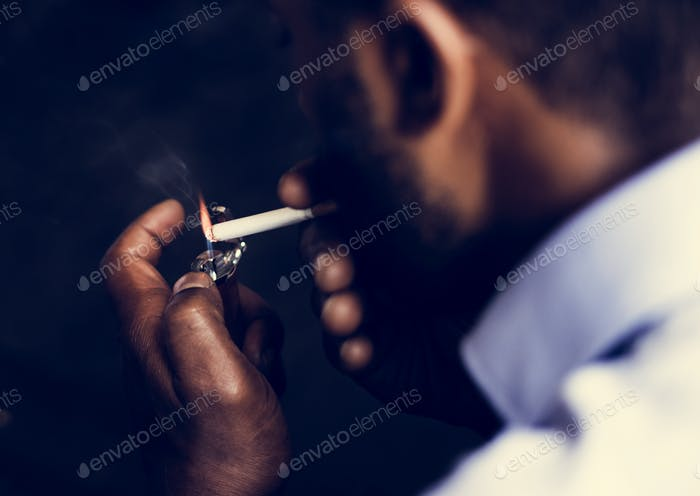 Rear view of man lighting a cigarette