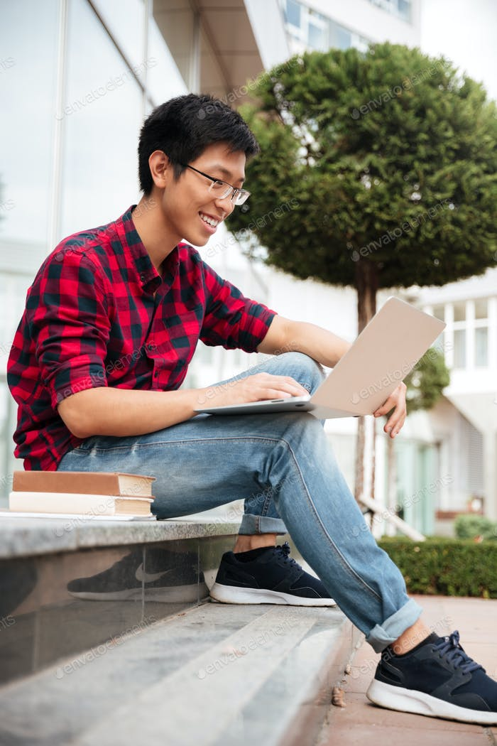Cheerful asian young man sitting and using laptop outdoors