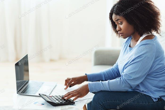 Schwarze Frau mit Taschenrechner und PC zu Hause