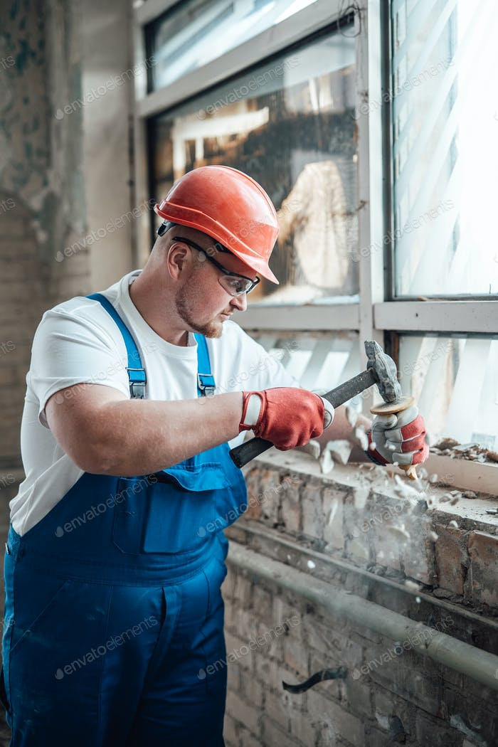 Contractor wielding a hammer to destroy old brick walls