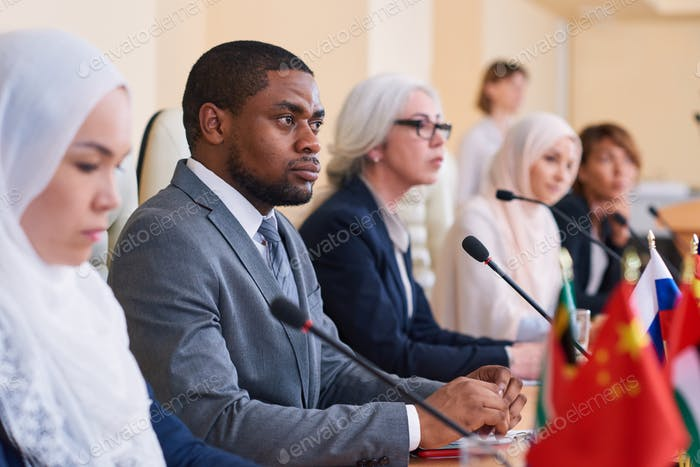 African-american businessman listening attentively to one of speakers report