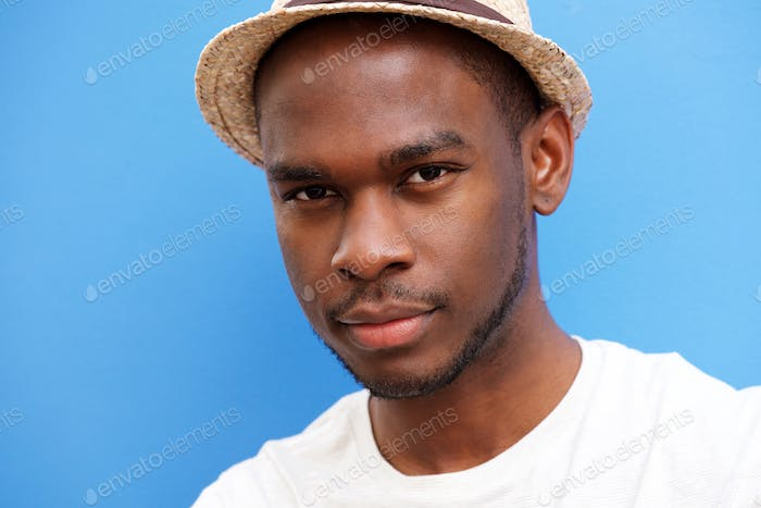 Close up cool young black guy with hat against blue background