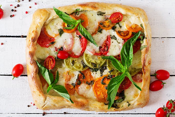 Mozzarella, tomatoes, basil savory pie on a white wooden background.