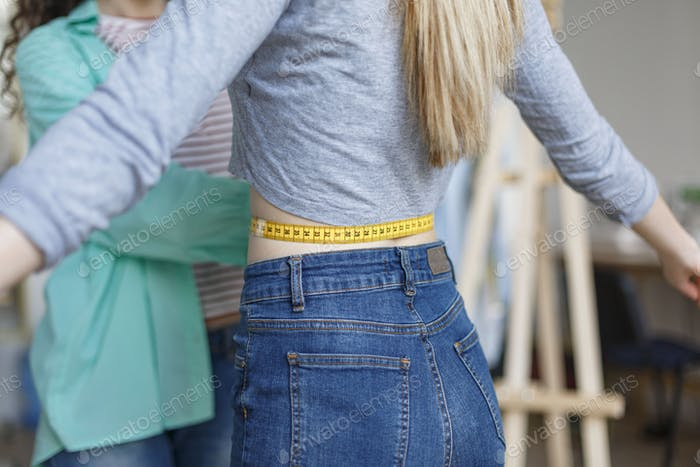 Close up designer measuring customer waist with tape in sewing w