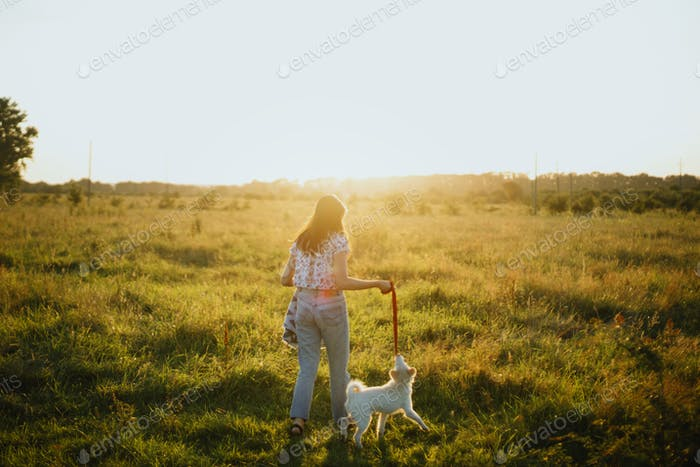 Stylish hipster girl walking with cute white puppy in summer meadow