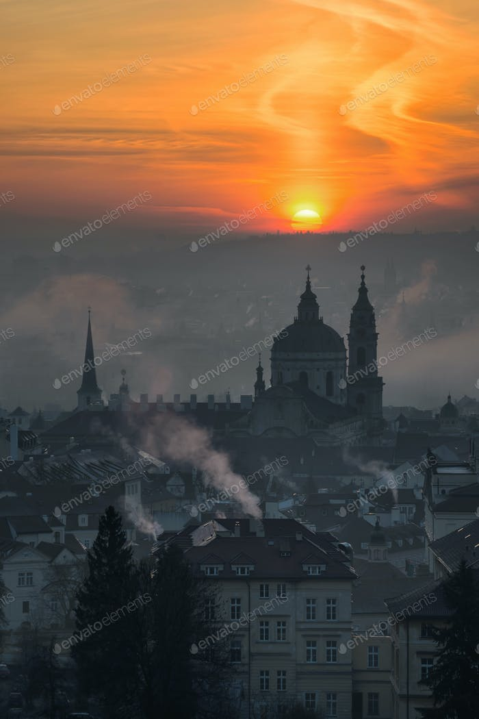 St. Nicolas church during foggy sunrise and amazing cloudy sky, Prague, Czech republic