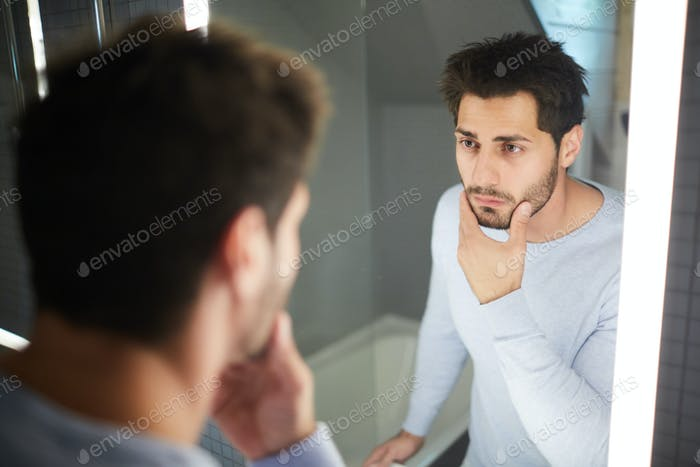 Handsome man touching beard and looking into mirror