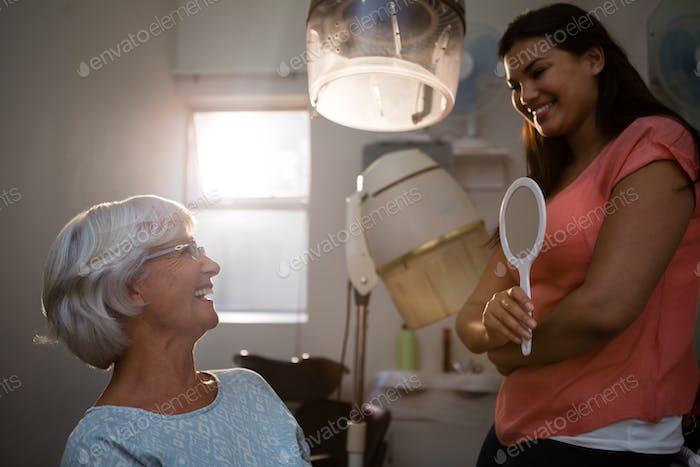 Hairstylist talking to senior woman