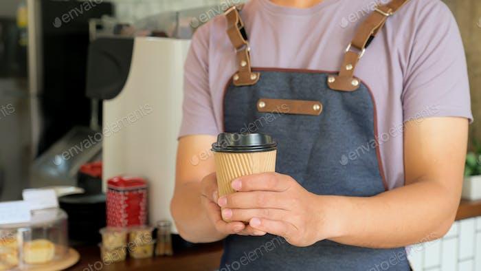 Barista hold a take away coffee mug send to customers.