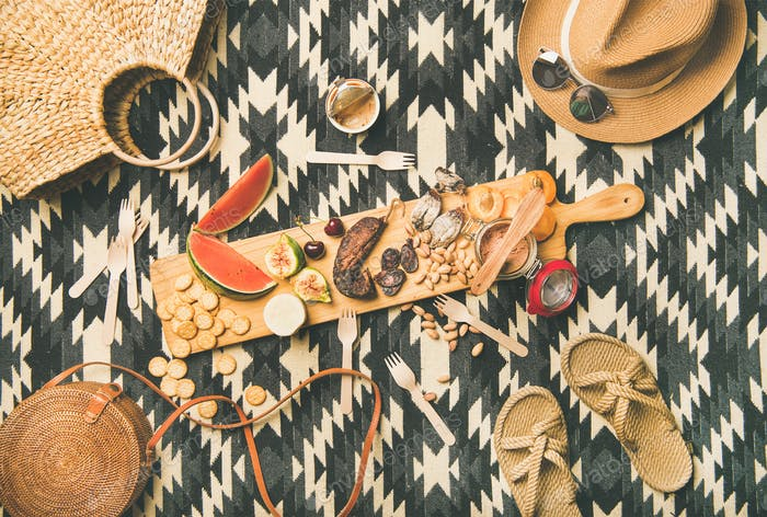 Picnic concept with sausage, fruit, cheese, pate and straw accessories