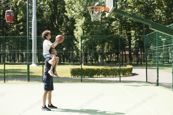 Man helping his son to score a basket